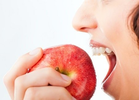 A woman wearing Invisalign in Cambridge and biting into an apple