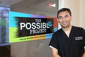 Dr. Abe in front of the possible project sign