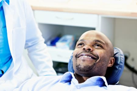 A man sitting in a dental chair being examined to see if he is a candidate for Invisalign in Cambridge